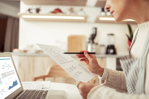 事業開発。彼女のラップトップと彼女のカフェの開発に取り組んでいる数枚の紙を持ってテーブルに座っている集中したスマートビジネスウーマン。