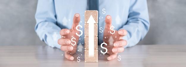 성공과 성장에 대한 사업 개발 concept.businessman 성장 그래프에 나무 블록을 배열하려고합니다.