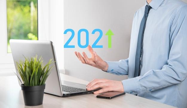 成功への事業開発と成長する成長2021年の概念。2021年の概念で事業成長グラフを計画する。ビジネスマンの計画と彼のビジネスの肯定的な指標の増加。