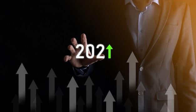 成功への事業開発と成長する成長2021年の概念。2021年の概念で事業成長グラフを計画する。ビジネスマンの計画と彼のビジネスの肯定的な指標の増加