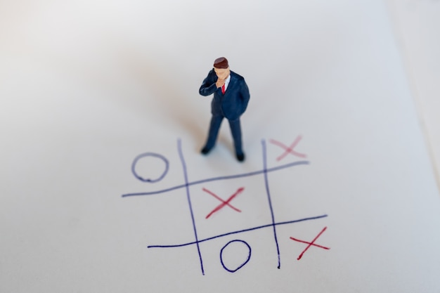 Business direction and planning concept. businessman miniature figure standing on paper with ox game