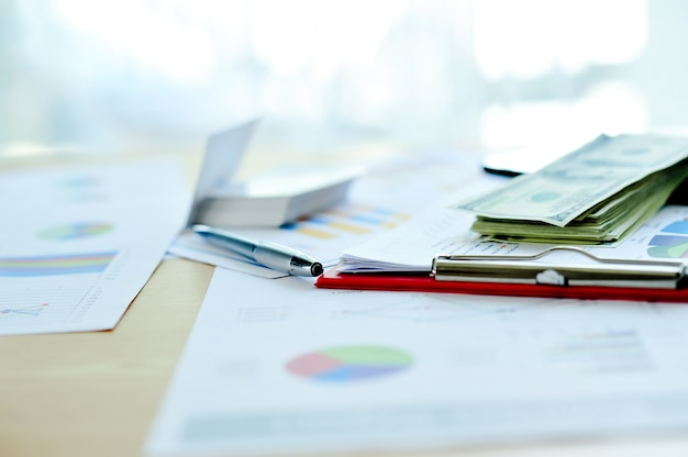 Business documents, financial graphs, and graphs on the work desk. blocked with multiple d
