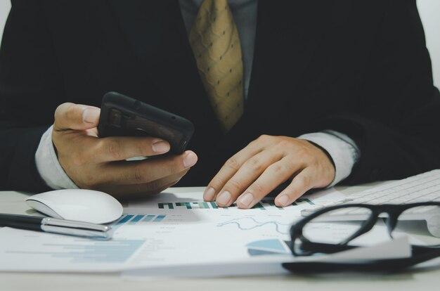 Деловые документы, графики и диаграммы финансовой отчетности и роста прибыли, держа мобильный телефон за столом