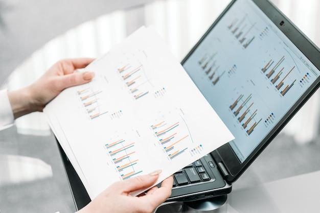 ビジネスドキュメントのグラフ。紙を持っている手。
