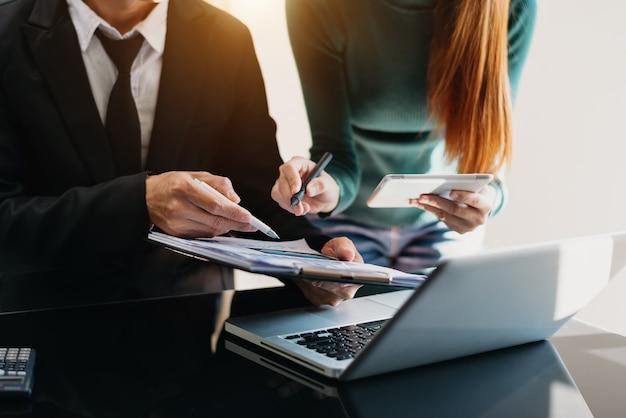 스마트 폰과 계산기 디지털 태블릿이 있는 사무실 테이블의 비즈니스 문서, 소셜 네트워크 다이어그램이 있는 그래프 비즈니스 및 사무실에서 작업하는 데이터에 대해 논의하는 두 명의 동료
