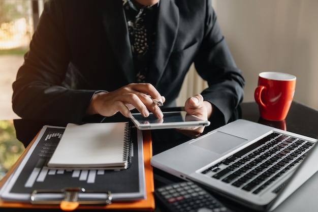 スマートフォンとデジタルタブレットを備えたオフィステーブルのビジネスドキュメントとグラフの財務と人間の作業