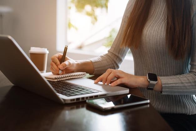 Деловые документы на офисном столе со смартфоном и цифровым планшетом и графиком, финансовым и работающим с женщиной
