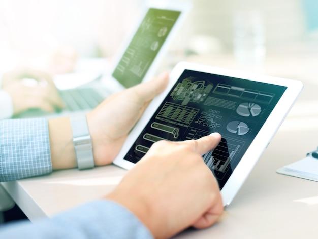 スマートフォンとラップトップコンピューターを使用したオフィステーブルのビジネスドキュメントと、ソーシャルネットワーク図とバックグラウンドでデータについて話し合っている3人の同僚とのグラフビジネス