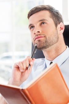 ビジネスの夢。彼の職場に座っている間、メモ帳を保持し、ペンで顎に触れるシャツとネクタイの思いやりのある若い男