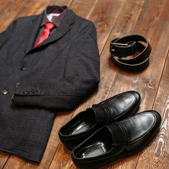 Деловой дресс-код. мужской костюм с обувью и поясом на темном дереве.