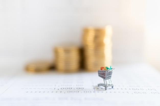ビジネスeコマースとお金の概念。コインとコピースペースのスタックで銀行通帳のショッピングカートまたはトロリーミニチュアフィギュアのクローズアップ。