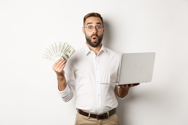 Business and e-commerce. man looking amazed with money income, working online, using laptop, standing