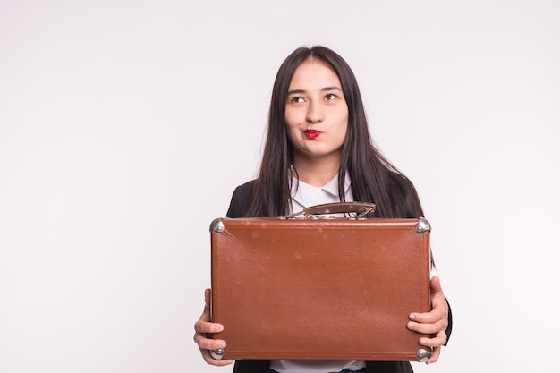 Business, emotions and people concept - young brunette girl keep a suitcase and thinking about a question on white wall with copy space