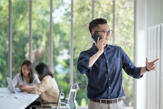 비즈니스 직원은 긍정적 인 태도로 회사 사무실에서 일하는 것을 즐기고 행복합니다.
