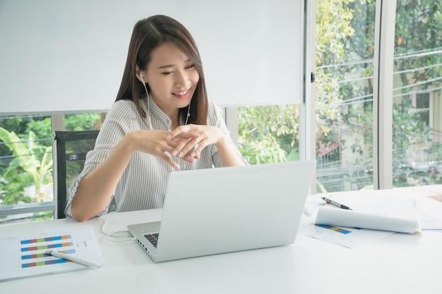 회사 사무실에서 인터넷 기술을 통해 동료와 화상 회의를 위해 노트북을 사용하는 비즈니스 직원.