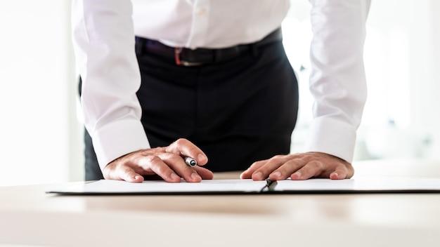 그의 책상 뒤에 서있는 신청서 또는 기타 중요한 문서에 서명하는 사업 고용주