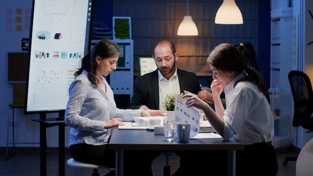 Business entrepreneur woman discussing with focused diverse multi ethnic teamwork analyzing company statistics working in office meeting room late at night. coworkers brainstorming ideas