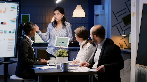 Business entrepreneur woman presenting management graphs using tablet working at company solution late at night in office meeting room. diverse multi-ethnic teamwork brainstorming financial strategy