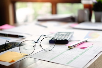 Business equipment glasses, data financial paper and calculator on office table.