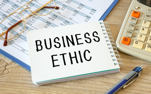 Business ethic is written on a notepad on an office desk with office accessories.