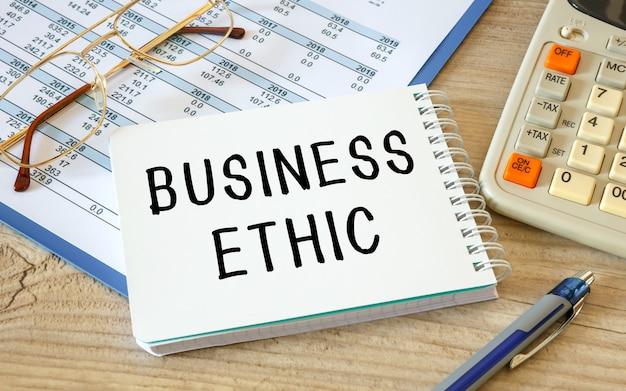 비즈니스 윤리는 사무실 액세서리와 함께 사무실 책상에 메모장에 기록됩니다.