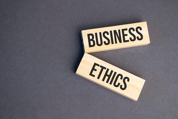 노란색 배경에 나무 블록에 비즈니스 윤리 단어. 비즈니스 윤리 개념입니다.