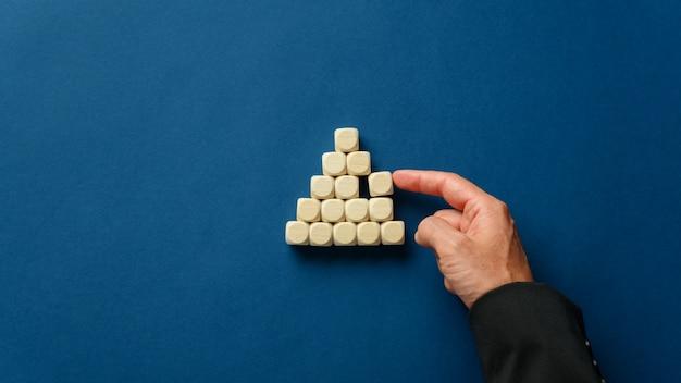 Деловой руководитель, строящий форму пирамиды с деревянными кубиками