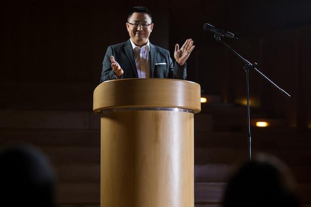 会議センターでスピーチをしながら拍手する経営者