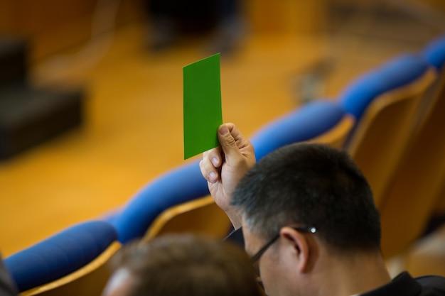 Деловой руководитель его одобрение, подняв руку в конференц-центре