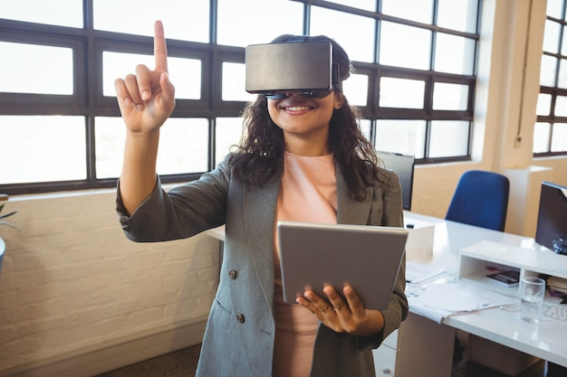Business executive holding digital tablet while using virtual reality headset
