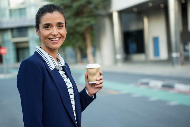 使い捨てのコーヒーカップを保持しているビジネスエグゼクティブ
