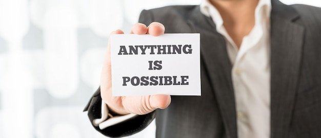 Business executive holding up a white card with anything is possible sign in order to motivate his team