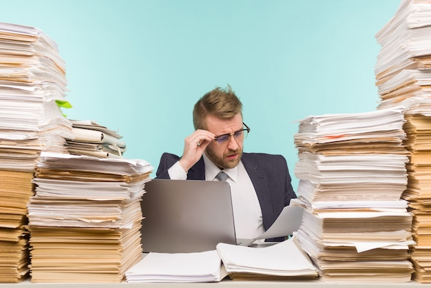 経営幹部はオフィスでビデオ会議を開催し、書類の山を抱えています。彼は仕事でいっぱいです。
