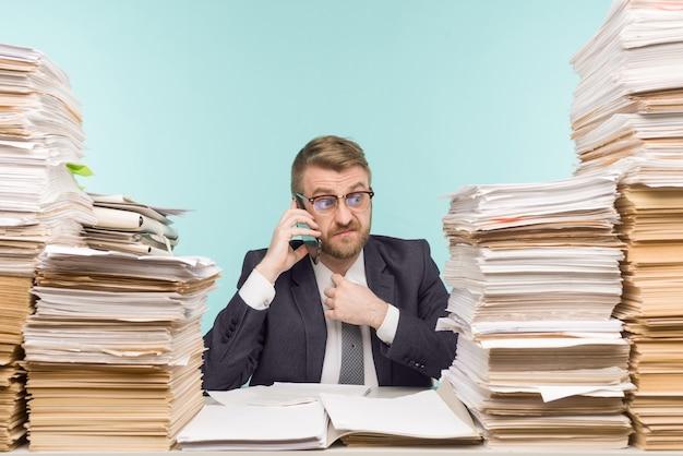オフィスの経営者と書類の山、不十分な仕事のために電話で叱られた-