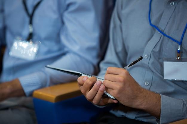 Деловой руководитель, участвующий в деловой встрече, делая заметки в конференц-центре
