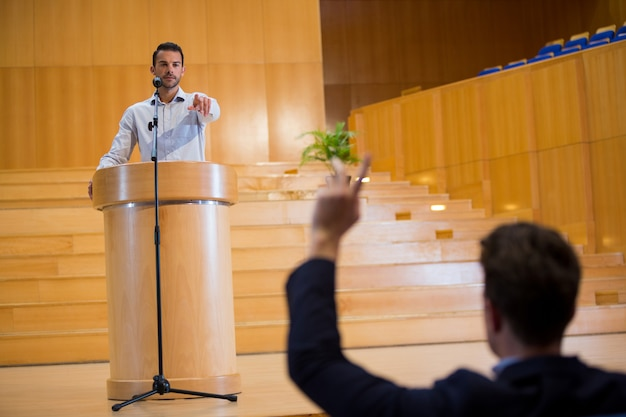 Business executive pointing towards audience while giving a speech
