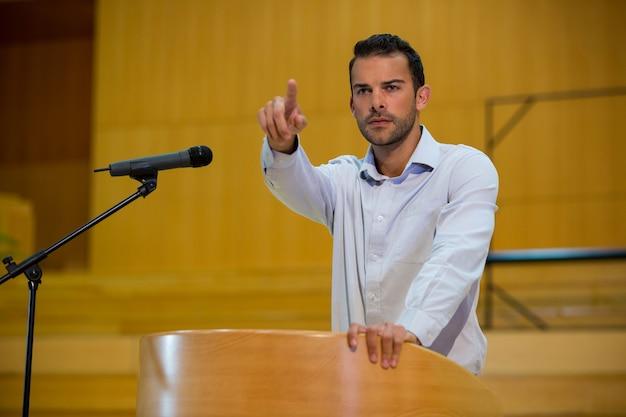 会議センターでスピーチをしながら指さし経営幹部