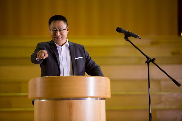 Business executive pointing while giving a speech at conference center