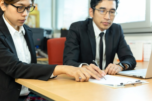 Business executive signing contracts with secretary at desk in office.