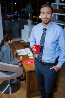 Business executive standing with a cup of coffee
