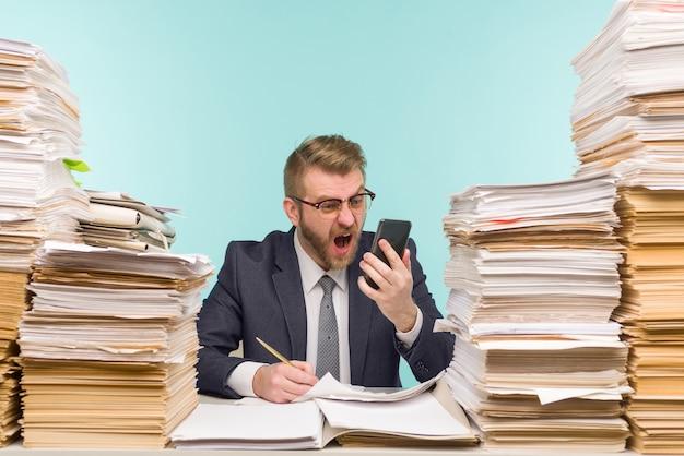 経営幹部は、オフィスでの仕事がうまくいかず、書類が山積みになっていることを電話で誓います。彼は仕事でいっぱいです-