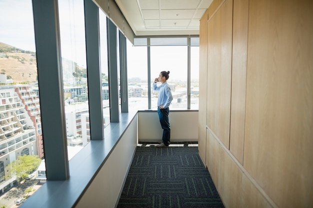 Business executive talking on mobile phone in corridor