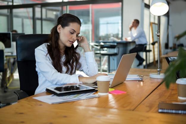 책상에서 노트북을 사용하는 동안 휴대 전화 통화 비즈니스 임원