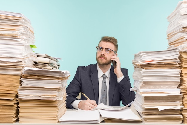 オフィスで働いている電話と書類の山で話している経営幹部は、仕事でいっぱいです-
