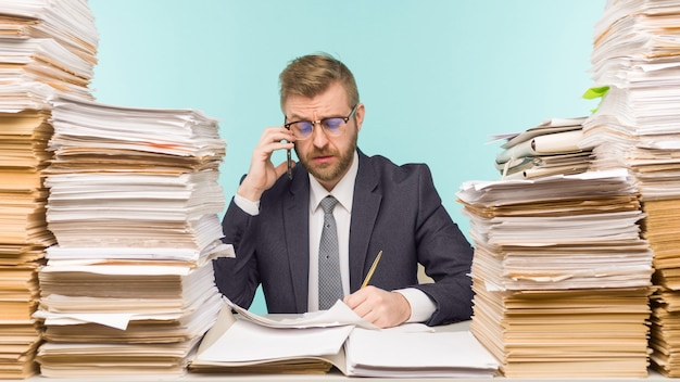 Business executive talking on the phone working in the office and piles of paperwork, he is overloaded with work - image