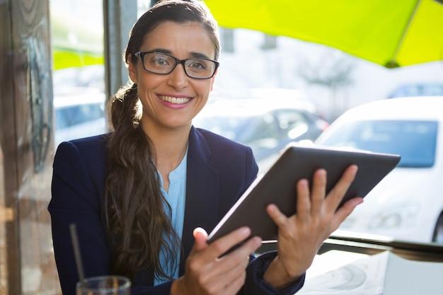 カフェでデジタルタブレットを使用してビジネスエグゼクティブ
