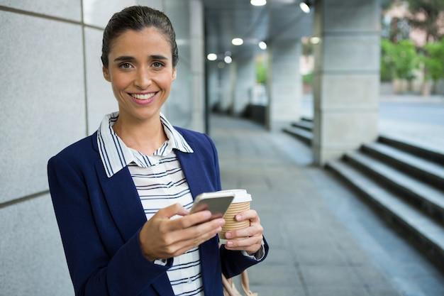 コーヒーを飲みながら携帯電話を使用してビジネスエグゼクティブ