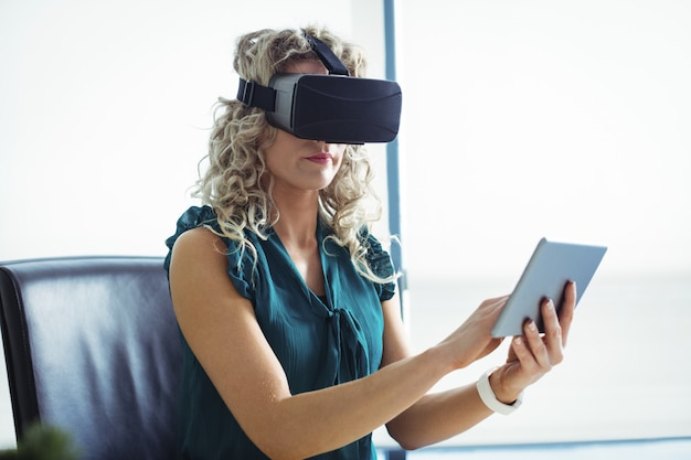 Business executive using virtual reality headset and digital tablet