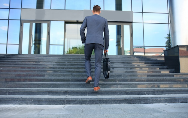 Business executive with briefcase going up the stairs.