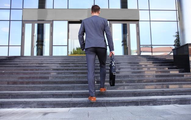 ブリーフケースを持って階段を上る経営者。